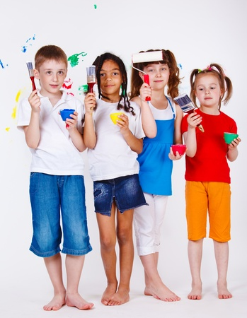 Four kids holding paintbrushes and paints in hands photo