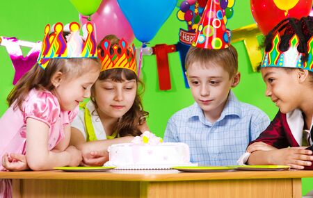 Hungry kids looking at birthday cake photo