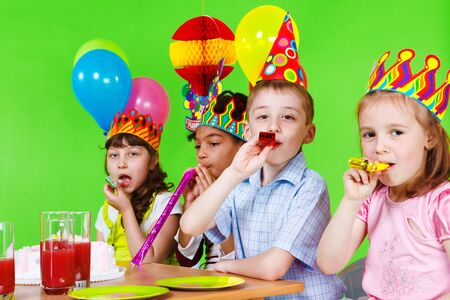 blow out: Kids blowing into party horns Stock Photo