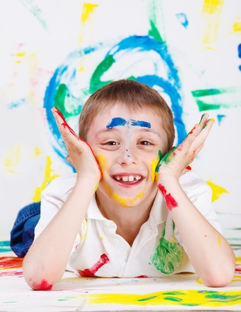 Cheerful boy with his face and hands painted photo
