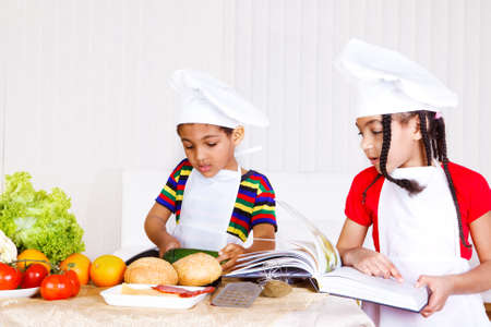 Two kids in white aprons and hats cooking photo