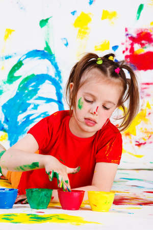 Lovely little girl dipping fingers into paint jar Stock Photo - 9587565
