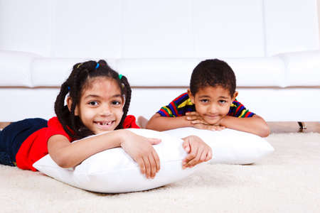 Laughing kids lying with pillows Stock Photo - 9587530