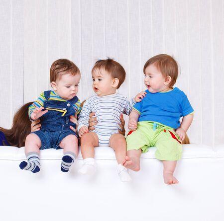Tres niños pequeños sentarse en la parte posterior del sofá