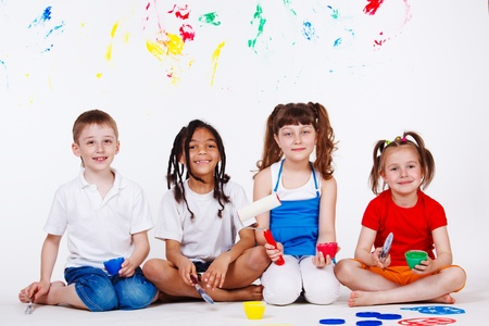 Lovely children with paintbrushes and paint roller photo