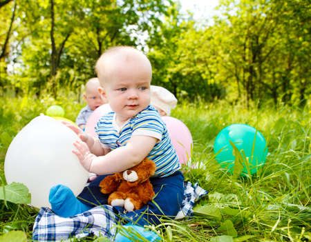 Babies playing with balloons in the park Stock Photo - 9587622