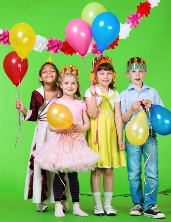 Laughing children holding balloons in hands photo