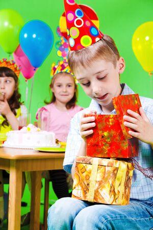 Preschool boy in party hat looking into present box photo