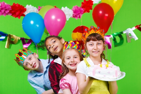 Laughing kids in party  hats and crowns holding birthday cake photo