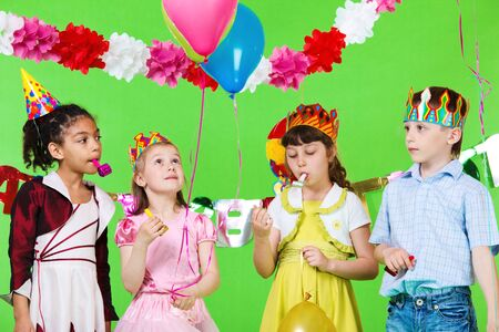 blowout: Four children with noisemakeras and balloons Stock Photo
