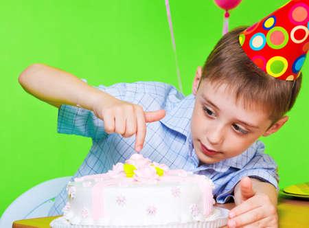 Little boy in party hat tasting birthday cake photo