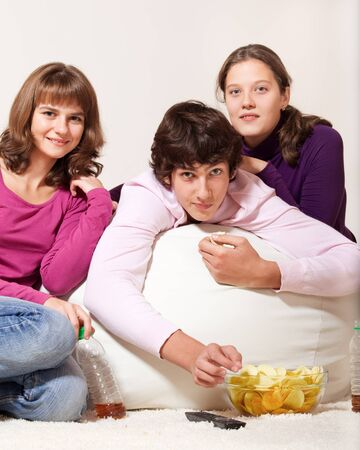 Friendly teens eating crisps and watching TV photo