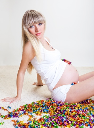 Pregnant woman sitting on the carpet among candies photo