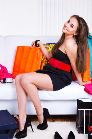 Joyful girl sitting on the sofa with lots of shopping bags and boxes photo