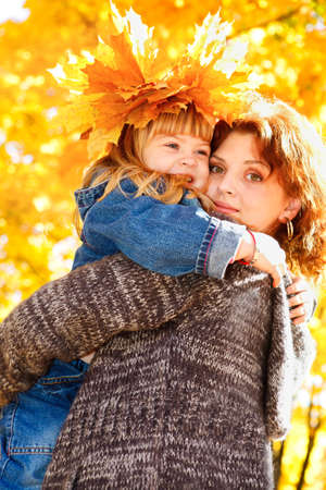 Mother embracing cheerful preschool daughter  in the autumn park photo