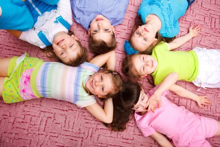 Kids lying on the floor in a circle photo