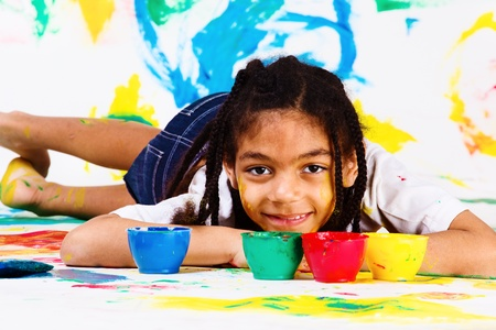 african education: African american girl lying, plastic jars with paints beside her Stock Photo