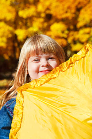 Preschool girl hiding behind yellow umbrella in the autumn park photo