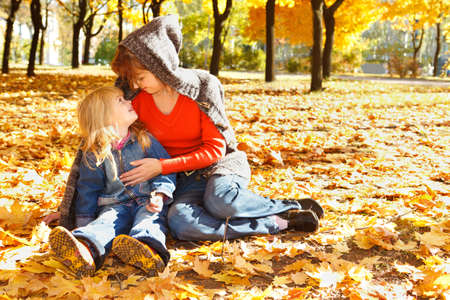 Happy mother and daughter sitting in autumn leaves photo