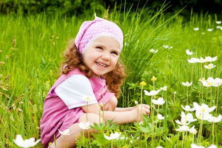 Laughing girl  on the meadow with white flowers photo