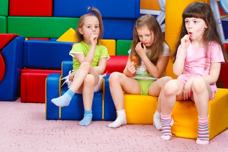 little girl sitting: Happy preschool girls eating  lollipops Stock Photo