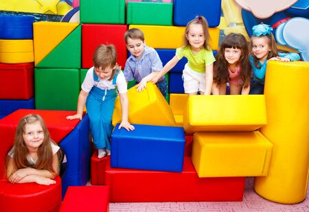 Group of joyful kids playing with large leather blocks photo