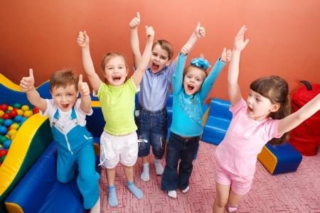 enfants qui rient: Groupe de cris des enfants avec les mains jusqu'�