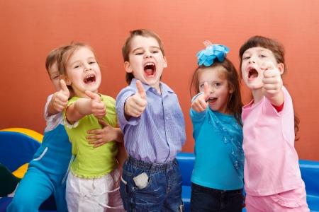 kinder: Grupo de ni�os alegres aparece pulgar