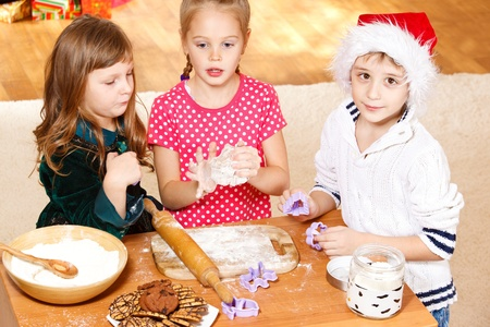 Three kids using dough cutters to make cookies photo