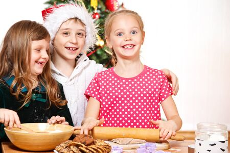 Three smiling kids cooking photo