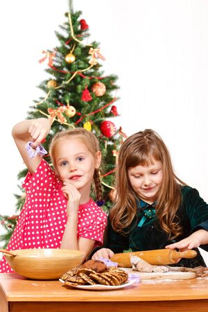 Two preschool girls making chocolate  cookies photo