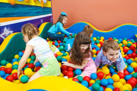 Joyful kids playing in the pool with colorful balls photo