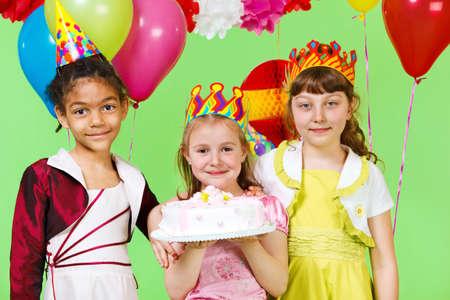 Three smiling girls holding birthday cake photo