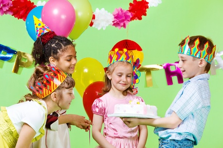 birthday celebration: Preschool boy offering birthday cake to his guests Stock Photo