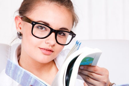 Closeup portrait  of a young woman in glasses reading photo