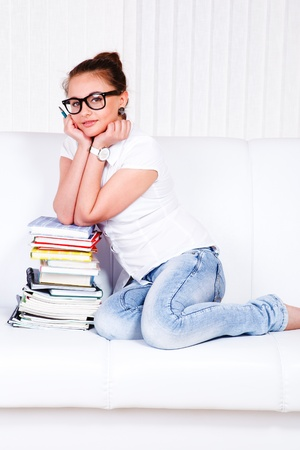 Beautiful teen sitting on the sofa with books stack photo