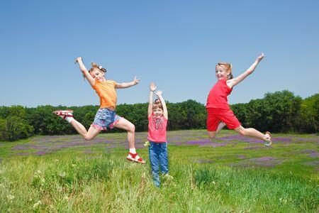 Three cheerful girls jumping outside photo