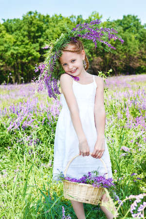 purple dress: Cute little girl holding  wicker basket with flowers Stock Photo