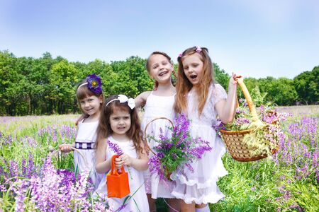 Four happy girls holding baskets with fresh flowers photo