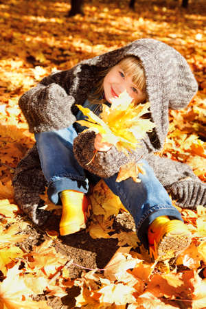 Lovely preschool girl sitting in an autumn park Stock Photo - 9670242