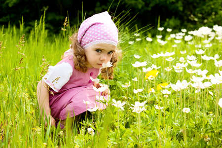 Happy girl  on the meadow smelling  white flowers photo