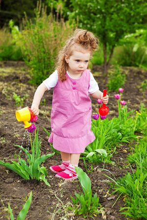 Cute curly girl watering flowers in the garden Stock Photo - 9670237