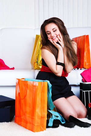 Happy teenage girl looking at shopping bags photo