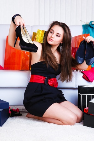 Lovely teenage girl choosing shoes photo