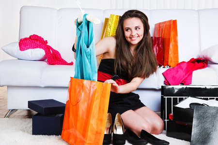 Girl taking new dress out of the shopping bag photo