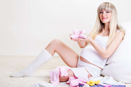 Happy pregnant woman holding pink baby bootees photo
