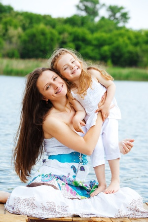 Happy mother and preschool girl in the outdoor photo