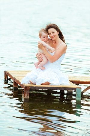 Attractive woman with baby in hands sitting on the wooden bridge photo