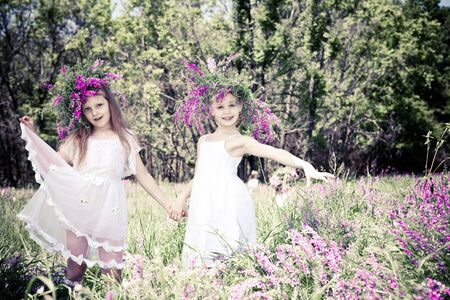 Two lovely girls with headwreaths, holding hands photo