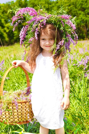 Preschool with floral wreath on head holding wicker basket photo